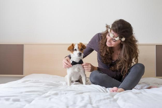 Bela jovem sentada na cama com seu cachorro pequeno bonito além. cachorro vestindo gravata borboleta e a menina está usando uma coroa de flores. casa, ambiente interno e estilo de vida