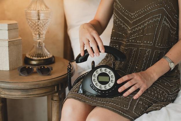 Bela jovem sentada na cama de um hotel, vestido elegante, segurando o fone, detalhes, close-up, mãos