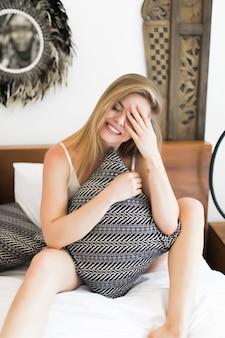Bela jovem sentada na cama em casa e abraçando a almofada