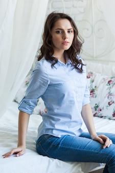 Bela jovem sentada na cama