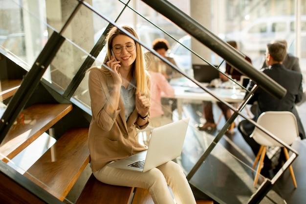 Bela jovem sentada na escada com um laptop e usando o telefone celular em um escritório moderno na frente de sua equipe