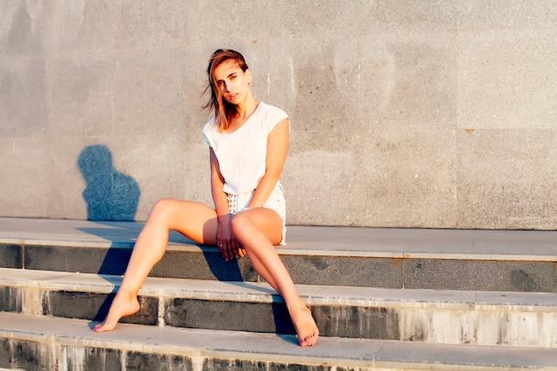 Bela jovem sentada na escada