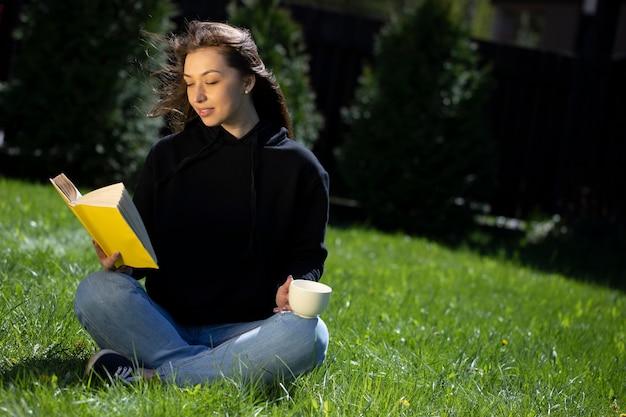 Bela jovem sentada na grama do parque com um livro de papel e uma xícara de chá descansando