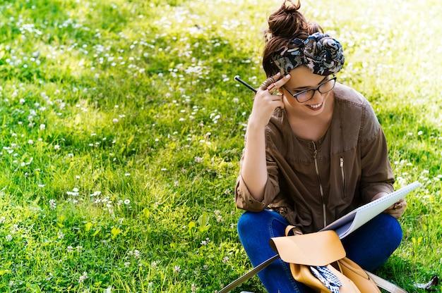 Bela jovem sentada na grama e lendo o livro ao ar livre