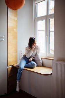 Bela jovem sentada na janela em jeans azul e camiseta branca
