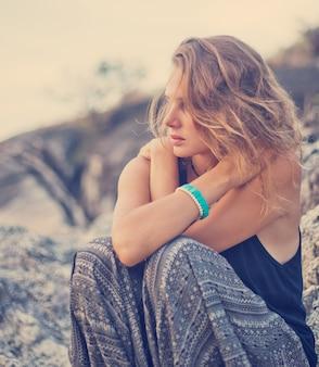 Bela jovem sentada nas pedras ao pôr do sol