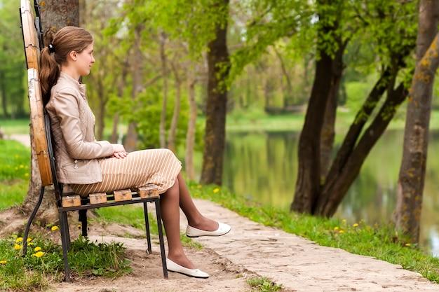 Bela jovem sentada no banco do parque, olhando para o futuro