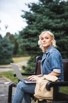 Bela jovem sentada no banco e usando telefone e laptop na cidade de manhã de outono