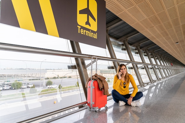 Bela jovem sentada no chão esperando no aeroporto com sua bagagem
