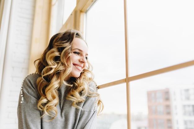 Bela jovem sentada no peitoril da janela, olhando pela janela sorrindo