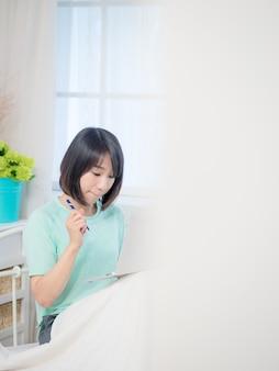Bela jovem sentada no quarto usando o laptop pela manhã