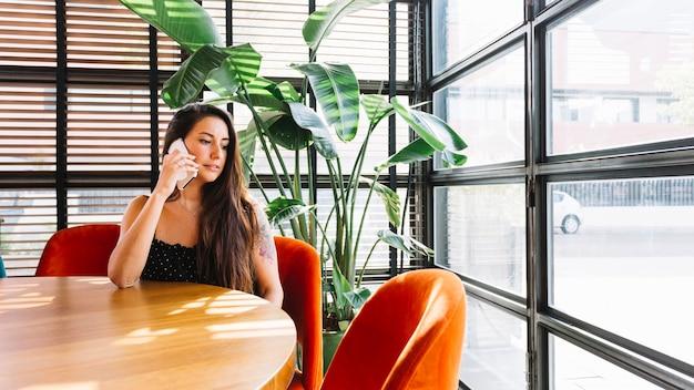 Bela jovem sentada no restaurante falando no celular