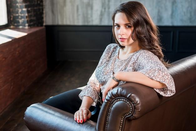 Bela jovem sentada no sofá olhando para a câmera