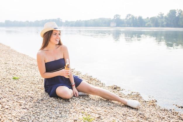 Bela jovem sentada perto da costa segurando a garrafa de cerveja de suco de fruta