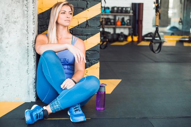 Bela jovem sentada perto da garrafa de água no clube de fitness