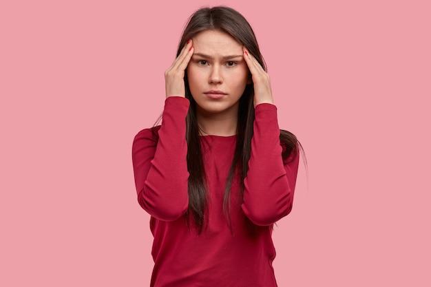 Bela jovem séria segura as têmporas, sente-se pressionada enquanto resolve o quebra-cabeça, usa um suéter vermelho, modelos contra um fundo rosa, está sobrecarregada