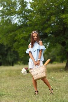 Bela jovem smilling mulher com flores na cesta de vime caminha no parque verde verão