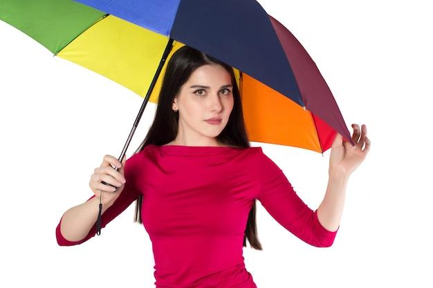 Bela jovem sob o guarda-chuva colorido, isolada no fundo branco