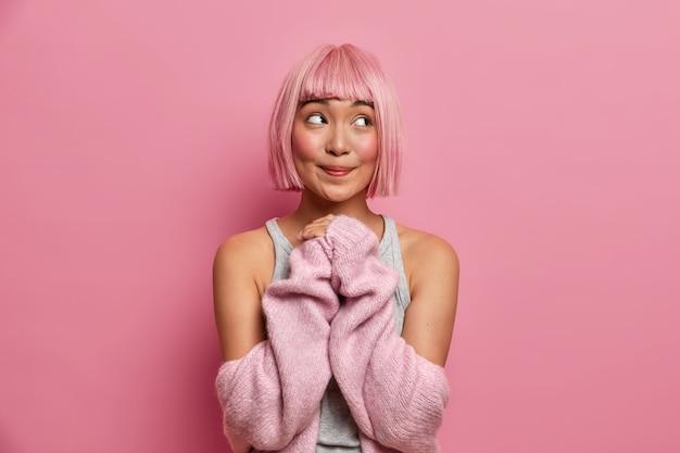 Bela jovem sonhadora de cabelo rosa, mantém as mãos unidas, veste um suéter quente com mangas baixas, mostra os ombros nus, posa dentro de casa, olha para longe