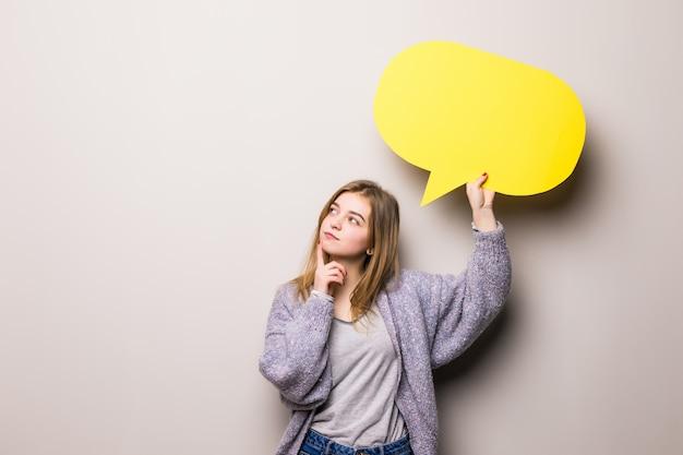 Bela jovem sonhadora segurando uma bolha amarela para texto, isolada