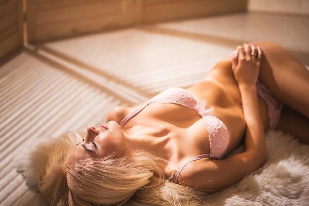 Bela jovem sonolenta e sensual com belas formas corporais em lingerie deitada sobre um pelo branco contra a superfície das cortinas e da luz do dia