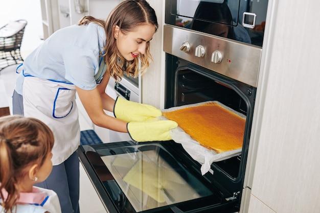 Bela jovem sorridente abrindo o forno e tirando a assadeira com bolo
