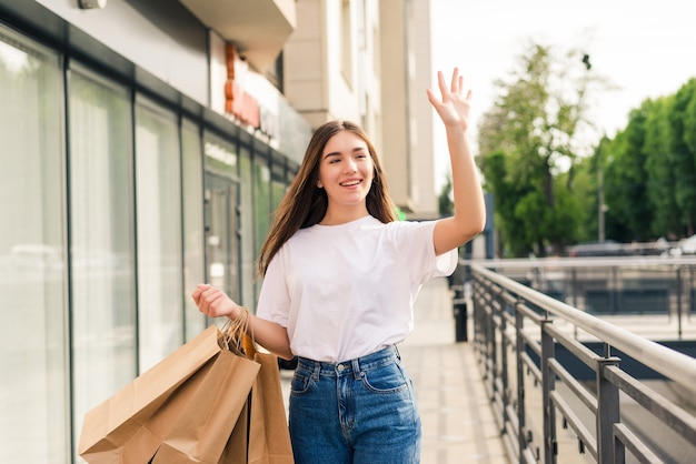 Bela jovem sorridente andando com sacolas de compras e acenando com a mão na rua da cidade. conceito de beleza, gesto e estilo de vida