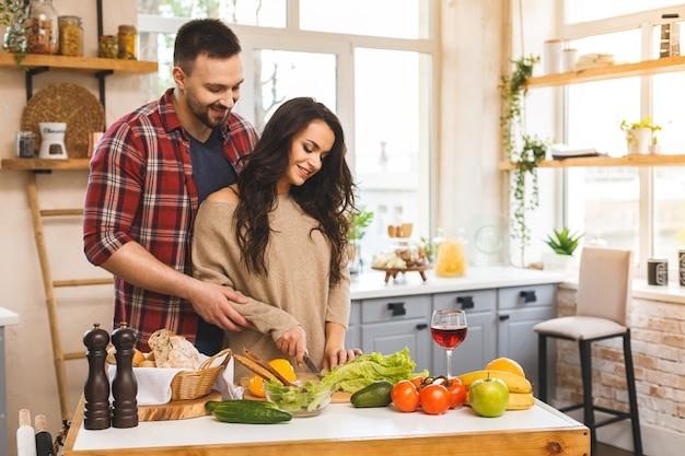 Bela jovem sorridente casal feliz está falando e sorrindo enquanto cozinha alimentos saudáveis na cozinha em casa.
