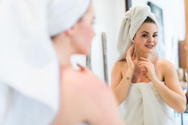 Bela jovem sorridente com roupão e toalha tocando o rosto enquanto olha para o espelho no banheiro