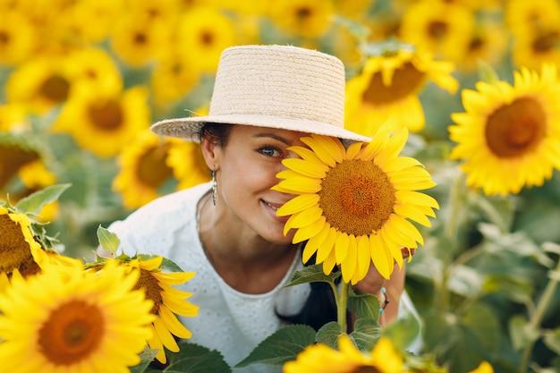 Bela jovem sorridente com um chapéu com uma flor no olho e rosto em um campo de girassóis