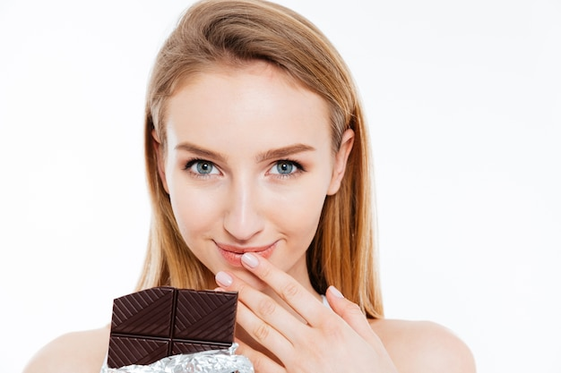 Bela jovem sorridente comendo barra de chocolate sobre fundo branco