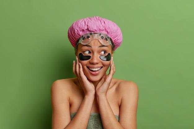 Bela jovem sorridente e satisfeita tocando o rosto aplica adesivos de colágeno preto usa chapéu à prova d'água e toalha embrulhada se sente feliz isolada na parede verde