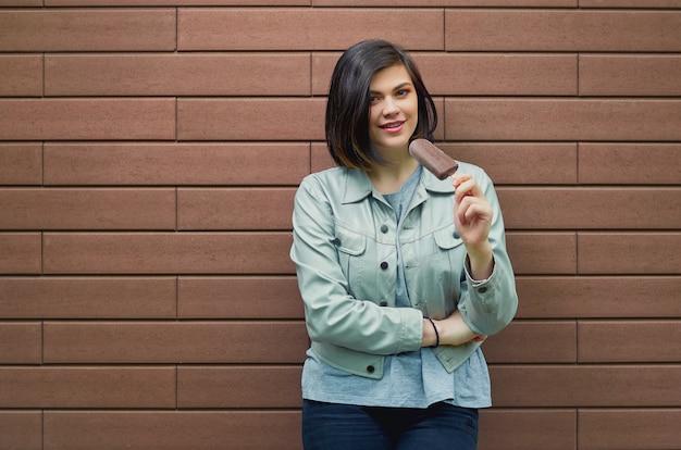 Bela jovem sorridente em uma jaqueta de couro elegante prova sorvete com cobertura de chocolate perto de uma parede de tijolo marrom texturizado.