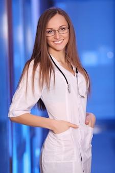 Bela jovem sorridente enfermeira no corredor do hospital