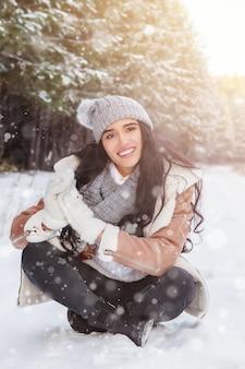 Bela jovem sorridente está sentada na estrada de inverno em um dia ensolarado na floresta de inverno e está nevando, feriados de natal ou ano novo, férias de inverno