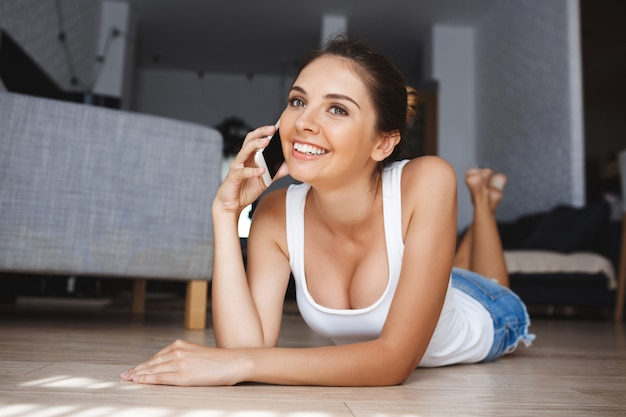 Bela jovem sorridente, falando no telefone, que estabelece no chão na sala de estar