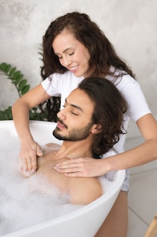 Bela jovem sorridente fazendo massagem no peito para o marido relaxando na banheira com água quente e espuma