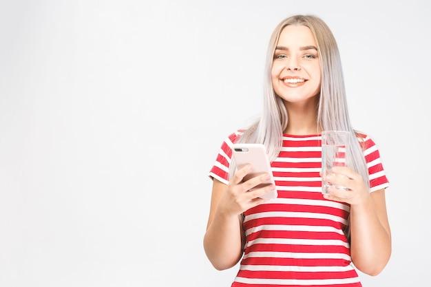 Bela jovem sorridente fica sobre fundo branco e olha para o telefone com um copo de água fria com o celular. isolado, mensagens de texto.