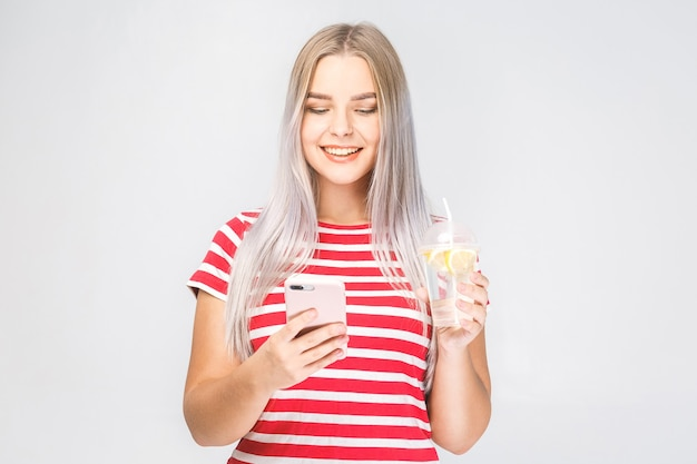 Bela jovem sorridente fica sobre um fundo branco e olha para o telefone com um copo de bebida gelada. isolado