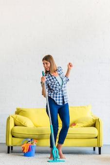 Bela jovem sorridente, limpando a casa cantando