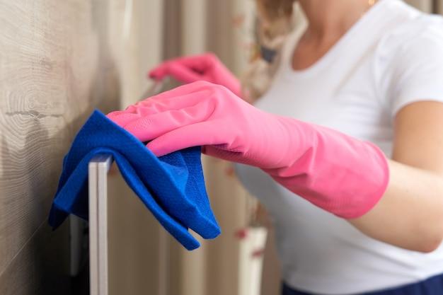 Bela jovem sorridente, limpando a casa com um pano de microfibra. mulher limpando a tevê com limpador em casa, close-up. jovem mulher feliz limpando os móveis da sala de estar em casa