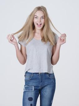 Bela jovem sorridente mulher caucasiana com longos cabelos loiros, posando em fundo branco.