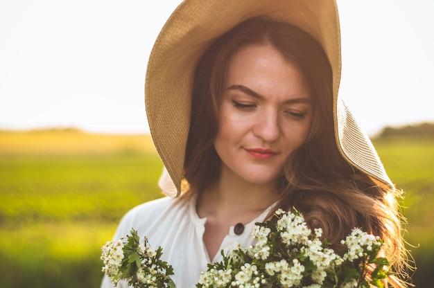 Bela jovem sorridente no vestido vintage e chapéu de palha em flores silvestres do campo. a menina está segurando uma cesta com flores