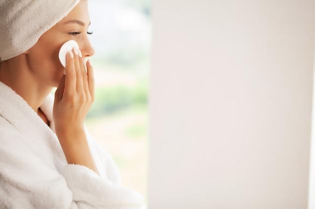 Bela jovem sorridente, removendo a maquiagem com um lenço facial.