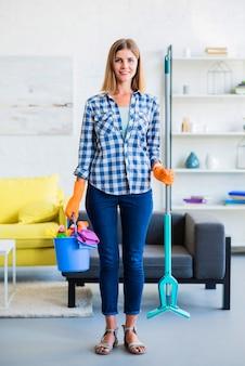 Bela jovem sorridente segurando o equipamento de limpeza nas mãos em casa