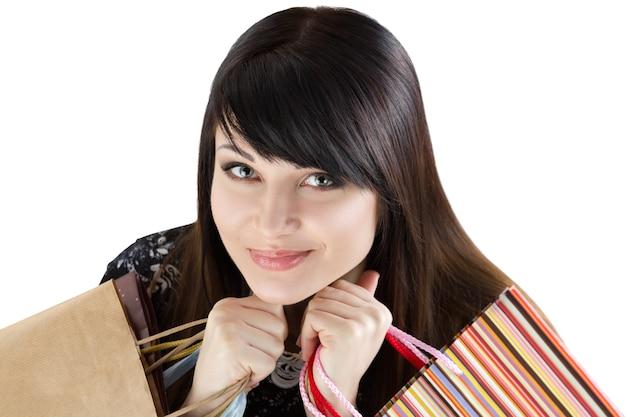 Bela jovem sorridente segurando sacos de papel com as compras. venda e conceito de compras