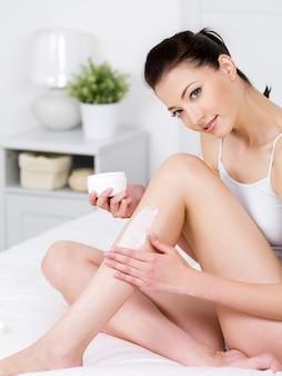 Bela jovem sorridente, sentada em uma cama e aplicando creme em suas atraentes pernas - vertical
