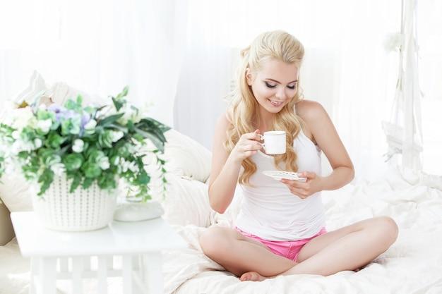 Bela jovem sorridente, sentada na cama branca, bebendo uma xícara de café