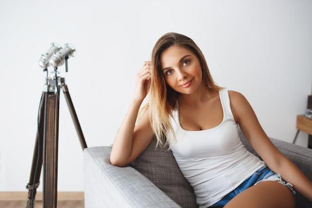 Bela jovem sorridente, sentado na poltrona na sala de estar