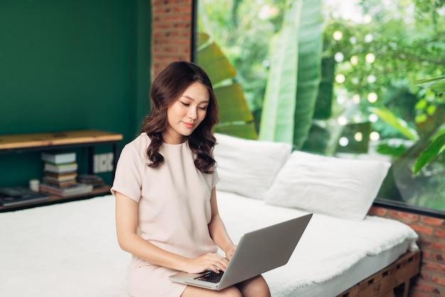 Bela jovem sorridente trabalhando no laptop enquanto está sentado na cama em casa perto de uma janela grande.